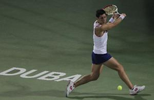 Carla Suarez Navarro of Spain returns the ball to Alize Cornet of France during the quarter final of Dubai Duty Free Tennis Championships in Dubai, United Arab Emirates, Thursday, Feb. 20, 2014