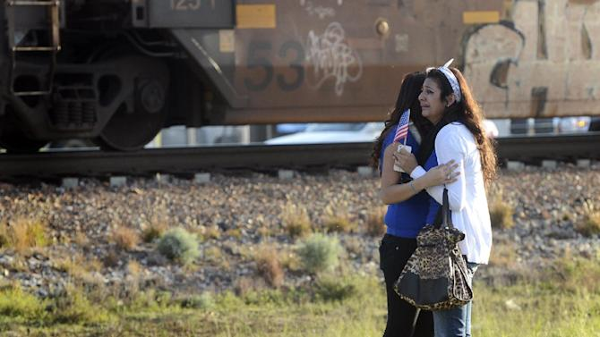 "Parade participants react after a trailer carrying wounded veterans in a parade was struck by a train in Midland, Texas, Thursday, Nov. 15, 2012. ""Show of Support"" president and founder Terry Johnson says there are ""multiple injuries"" after a Union Pacific train slammed into the trailer, killing at least four people and injuring 17 others. (AP Photo/Reporter-Telegram, James Durbin)"