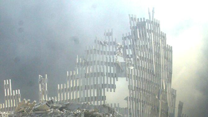 FILE - In this Sept. 11, 2001 file photo, a shell of what was once part of the facade of one of the twin towers of New York's World Trade Center rises above the rubble that remains after both towers were destroyed in the terrorist attacks. A federal health official is expected to announce in early June, 2012, whether people with cancer will be covered by an aid program for New Yorkers sickened by World Trade Center dust. An advisory committee recommended in March that the government open up the $4.3 billion program to people who developed cancers after being exposed to the toxic soot that fell on Manhattan when the towers collapsed. (AP Photo/Shawn Baldwin, File)