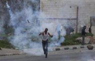 A protester throws back a tear gas canister fired by Israeli troops during clashes outside Israel's Ofer military prison near the West Bank city of Ramallah February 22, 2013. Israeli forces clashed with Palestinian protesters throughout the occupied West Bank on Friday, capping a week of violence amid a hunger strike by four Palestinians in Israeli jails. REUTERS/Mohamad Torokman