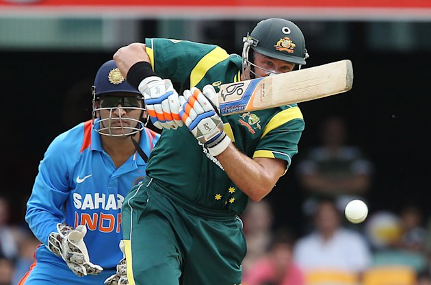 Australia's Mike Hussey plays a shot as India's wicket keeper MS Dhoni looks on during the One Day International cricket match between Australia and India in Brisbane, Australia, Sunday, Feb. 19, 2012