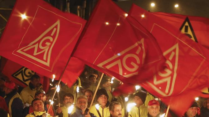 Night shift workers of the Ford car factory in the Cologne suburb of Niehl, hold flaming torches and flags of Germany's engineering and metal workers union IG Metall, during a temporary walkout for higher wages