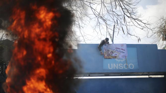 Flames from burning tyre is seen as boy puts sign at gate of headquarters of UN Special Coordinator during protest against decision by main U.N. aid agency to suspend payments to Palestinians for repairs to homes damaged in last summer's war, in Gaza