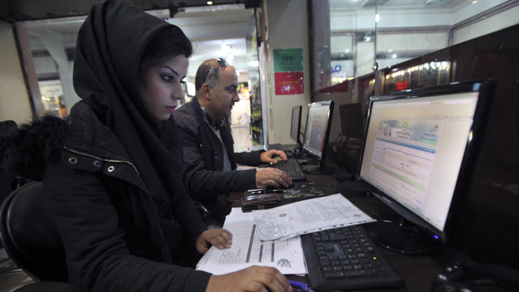 FILE - In this Sunday, Jan. 6, 2013, file photo, Iranians surf the web in an Internet cafe at a shopping center in central Tehran, Iran. Iran's entire Cabinet, that started in August 2013, has opened Facebook pages in what is seen as a move toward greater government openness, even though the social media site is blocked in the Islamic Republic. (AP Photo/Vahid Salemi, File)