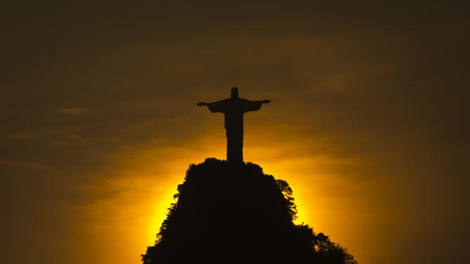 FILE - In this Friday, Dec. 28, 2012 file photo, the sun sets behind the Christ the Redeemer statue and the Corcovado mountain in Rio de Janeiro, Brazil, two days after the city recorded its hottest day since 1915 at 43 degrees Celsius (109.7 degrees Fahrenheit). New weather data shows that the world's average temperature in 2012 barely slipped into the top 10 hottest years on record, despite the U.S. smashing heat marks. The National Oceanic and Atmospheric Administration says last year's world average temperature was 58 degrees Fahrenheit (14.5 degrees Celsius) - a full degree above the 20th century average of 57 F (13.9 C). NASA, which measures temperatures differently, ranks 2012 as ninth warmest. Both agencies announced the data Tuesday, Jan. 15, 2013. (AP Photo/Felipe Dana)