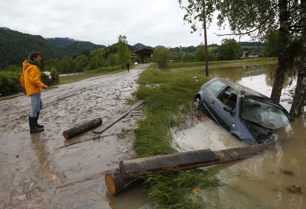 Man stands next to a damaged car after flooding in Austrian village of Koessen