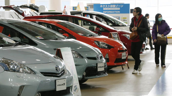Visitors browse a Toyota showroom in Tokyo,Tuesday, Feb. 5, 2013.  Toyota Motor Corp. reported its October-December profit rose 23 percent to 99.91 billion yen ($1.09 billion), compared to the same period the previous year, as sales jumped, especially in the U.S. Toyota also raised its projections Tuesday for the fiscal year through March.  (AP Photo/Koji Sasahara)