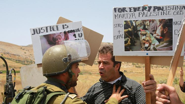 A Palestinian protester holds a picture of victims as he argues with an Israeli soldier during a protest against Israeli air strikes on Gaza, at Hawara checkpoint near Nablus