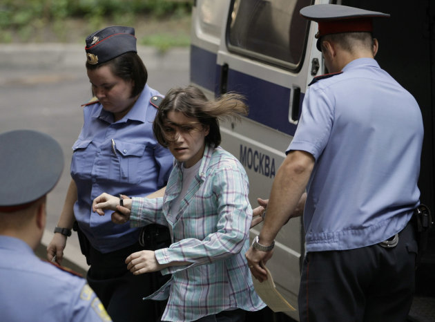 "Maria Alekhina, center, a member of feminist punk group Pussy Riot is escorted to a court room in Moscow, Russia, Monday, July 30, 2012. Three members of the band are facing trial for performing a ""pu"