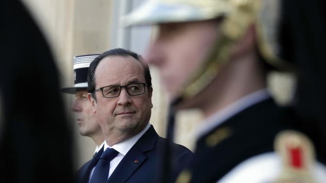 French President Hollande waits for guests to leave the Elysee Palace in Paris