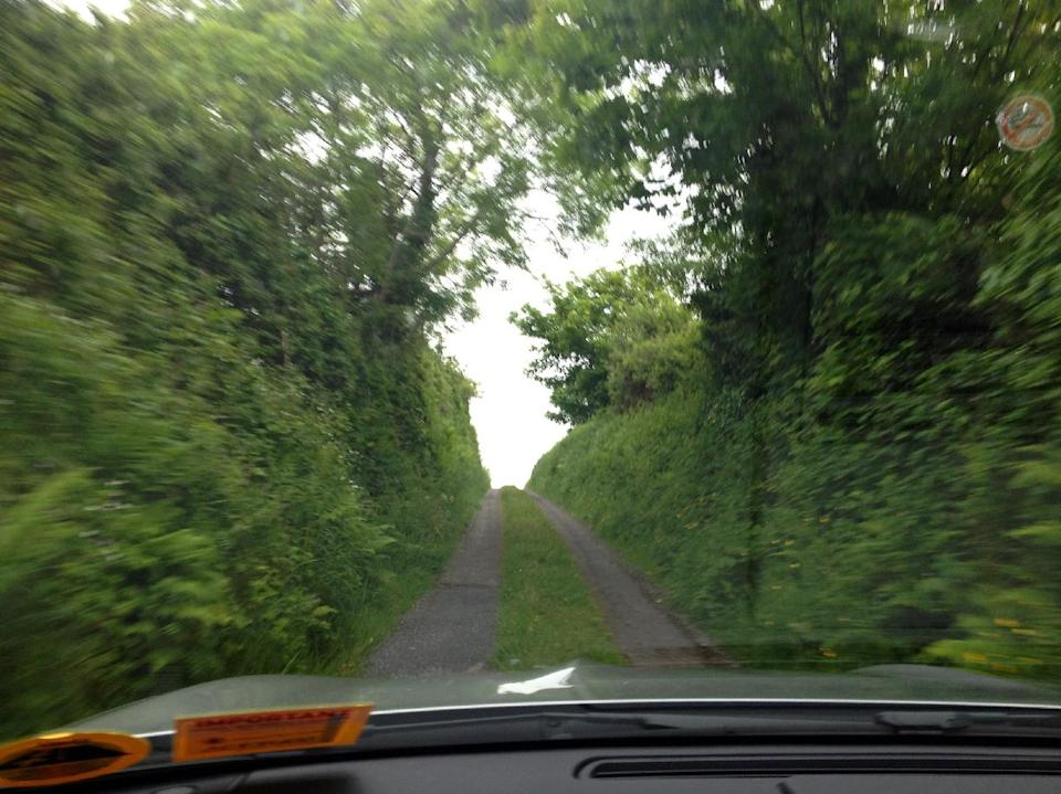 This May 31, 2012 photo shows a car driving along a narrow road in Mullaghmore, County Sligo, Ireland. Ireland is about 300 miles from north to south and a driving trip in the country's western region takes you along hilly, narrow roads with spectacular views ranging from seaside cliffs to verdant farmland. (AP Photo/Jake Coyle)