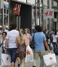 FILE - In this Aug. 4, 2011 file photo, shoppers, carrying their purchases, pass H&M, in New York. Consumers spent more on autos, furniture and gasoline in July, pushing up retail sales by the largest amount in four months. The gain could signal that Americans are a little more confident and help dispell fears that the country is in danger of toppling into another recession. (AP Photo/Frank Franklin II)