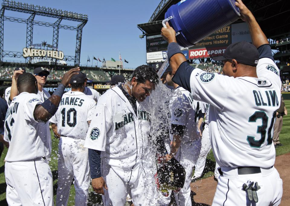 Seattle Mariners pitcher Felix Hernandez, center, is doused with water by teammate Miguel Olivo (30) after tossing a perfect game in a 1-0 win over the Tampa Bay Rays in a baseball game, Wednesday, Aug. 15, 2012, in Seattle. (AP Photo/Ted S. Warren)
