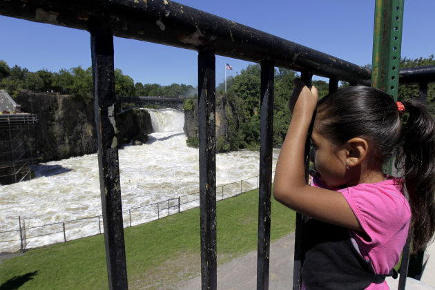 Jesery Gonzalez, 5, looks on as water rushes down the Great Falls as the Passaic River neared its cresting point following Hurricane Irene, Tuesday, Aug. 30, 2011, in Paterson, N.J. Many questions fac