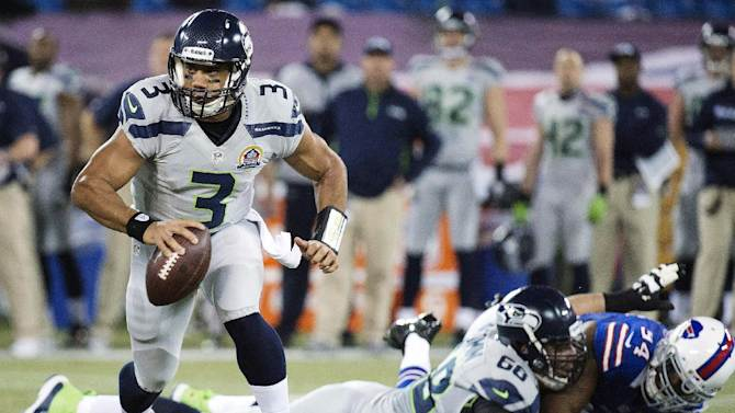 Seattle Seahawks quarterback Russell Wilson (3) runs the ball against the Buffalo Bills during the first the half of an NFL football game in Toronto, Sunday, Dec. 16, 2012. (AP Photo/The Canadian Press, Nathan Denette)