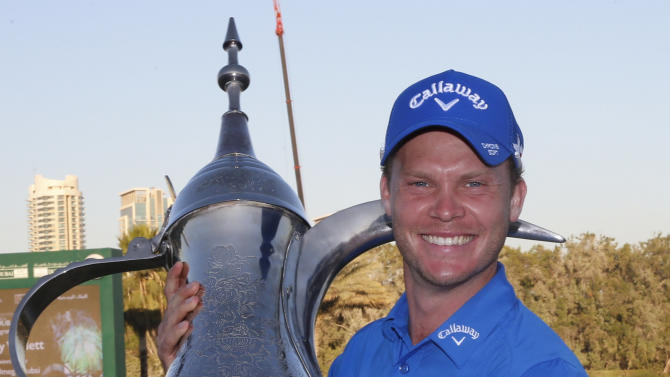 Willett of England holds his trophy after winning the Dubai Desert Classic golf championship