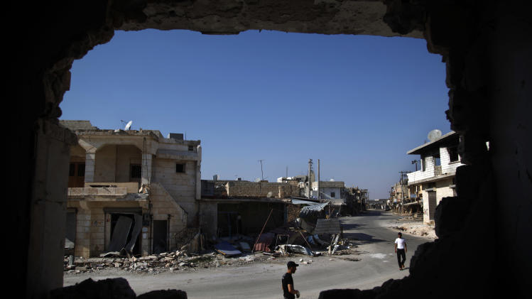 In this Sunday Aug. 5, 2012 photo,  Syrians are seen through a destroyed wall as they walk on a street in town of Atareb outskirts of Aleppo, Syria, Sunday, Aug. 5, 2012. (AP Photo)