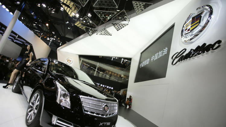 In this Sunday, April 21, 2013 photo, a model poses with a Cadillac XTS displayed at the Shanghai International Automobile Industry Exhibition in Shanghai, China. General Motors' global sales grew almost 4 percent in the first half of the year, enough to fend off Volkswagen to keep second place and perhaps bring the Detroit company closer to sales leader Toyota, according to GM, Tuesday, July 16, 2013. (AP Photo/Eugene Hoshiko)