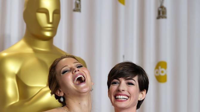 """Jennifer Lawrence with her award for best actress in a leading role for """"Silver Linings Playbook"""" and Anne Hathaway with her award for best actress in a supporting role for """"Les Miserables"""" pose during the Oscars at the Dolby Theatre on Sunday Feb. 24, 2013, in Los Angeles. (Photo by John Shearer/Invision/AP)"""