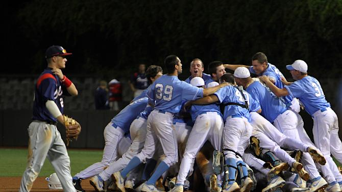 North Carolina celebrates their 12-11 win over Florida Atlantic in 13 innings during an NCAA college regional championship baseball game in Chapel Hill, N.C., Monday, June 3, 2013, as Florida Atlantic's Brendon Sanger, left, walks off the field. (AP Photo/Ted Richardson)