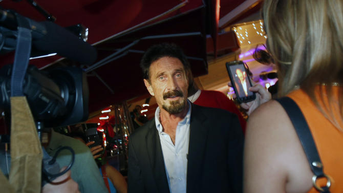 A television reporter takes a photo with her mobile phone of anti-virus software founder John McAfee, center, as he walks on Ocean Drive in the South Beach area of Miami Beach, Fla., on his way to dinner Wednesday, Dec 12, 2012. McAfee arrived in the U.S. on Wednesday night after being deported from Guatemala, where he had sought refuge to evade police questioning in the killing of a man in neighboring Belize.(AP Photo/Alan Diaz)