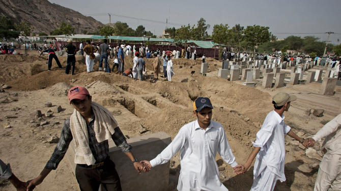 In this picture taken on May 29, 2010, people from a minority Muslim Ahmadi Community stand guard as others preparing to bury the victims of attack by Islamic militants, in Rabwa, some 150 kilometers (93 miles) northwest from Lahore Pakistan. The first Pakistani Nobel Prize laureate Professor Abdus Salam, the country's greatest scientist, who passed away in 1996, has been disowned by many of Pakistan's 190 million citizens because he was a member of a minority Muslim sect that has been persecuted by the government and targeted by Taliban militants who view Ahmadis as heretics. (AP Photo/Anjum Naveed)