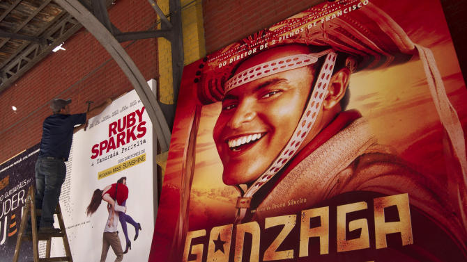 """A worker hangs a poster promoting the Brazilian film """"Gonzaga - from Father to Son"""" in Rio de Janeiro, Brazil, Friday, Sept. 28, 2012. The Rio de Janeiro International Film Festival is flooding this metropolis with hundreds of movies. The festival that launched late Thursday is Latin America's largest in terms of sheer volume, with feature films, documentaries, shorts and children's movies from more than 60 countries. (AP Photo/Silvia Izquierdo)"""