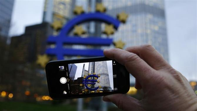 A man uses his mobile phone to take a picture of the euro sculpture outside the head quarters of the European Central Bank in Frankfurt
