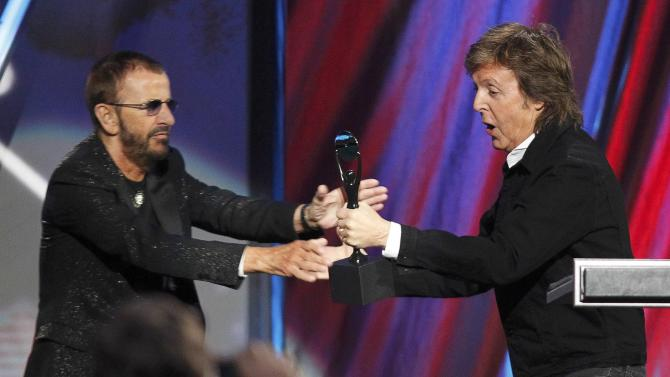 Starr reaches for his award after being inducted by McCartney during the 2015 Rock and Roll Hall of Fame Induction Ceremony in Cleveland