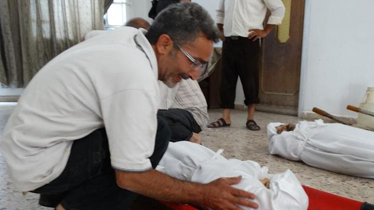 A relative weeps over the body of one of his family members killed during the alleged toxic gas attack in the Ghouta district of Damascus in August