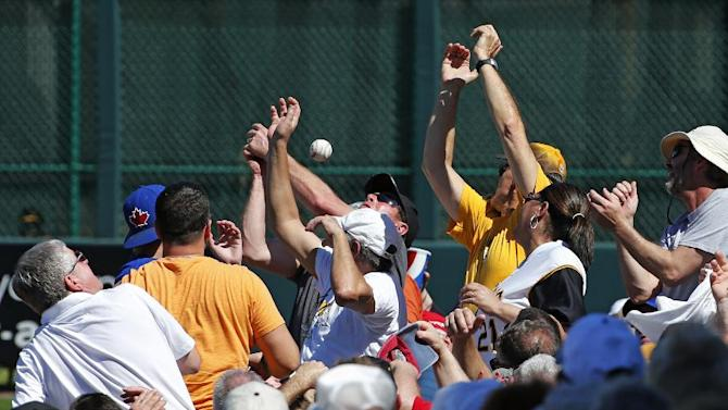 Fans reach for a foul ball down the first baseline during a spring training exhibition baseball game between the Pittsburgh Pirates and the Toronto Blue Jays in Bradenton, Fla., Wednesday, March 4, 2015.  (AP Photo/Gene J. Puskar)