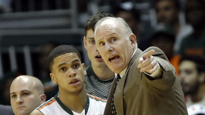 Miami head coach Jim Larranaga, right, talks with guard Manu Lecomte (20) in the second half of an NCAA college basketball game, against South Alabama, Friday, Nov. 28, 2014, in Coral Gables, Fla. Miami defeated South Alabama 87-75. (AP Photo/Lynne Sladky)