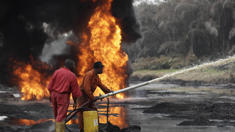 Fire fighters try to contain flames  from a burning oil pipeline in Ijeododo outskirt of  Lagos, Nigeria  Thursday, Dec. 20, 2012. The oil pipeline belonging to Nigeria National Petroleum Cooperation exploded near Nigeria's largest city as thieves tried to siphon oil from it  Monday. (AP Photo/Sunday Alambai