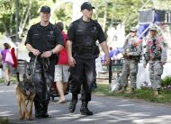 Massachusetts State Police patrol with a bomb sniffing dog before rehearsal for the Boston Pops Fourth of July concert at the Hatch Shell in Boston, Wednesday, July 3, 2013. The concert is city's first large public gathering since the Boston Marathon bombings. (AP Photo/Michael Dwyer)