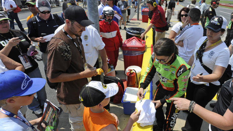 Danica Patrick signs autographs before qualifying for the NASCAR History 300 Nationwide series auto race in Concord, N.C., Saturday, May 26, 2012. (AP Photo/Mike McCarn)