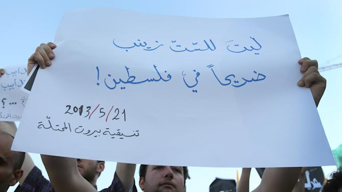 """A Lebanese activist holds up an Arabic placard reading: """"hope there was a shrine of Sayeda Zeinab in Palestine, (Sayeda Zeinab is the granddaughter of Islam's prophet Muhammad),"""" during a protest against the participation of Hezbollah members in the fighting in the Syrian town of Qusair, at the Martyrs square in Beirut, Lebanon, Tuesday May 21, 2013. Backed by elite troops of Lebanon's militant Hezbollah group, Syrian government forces fought rebels in a strategic opposition-held Syrian town near the Lebanese border for the third straight day Tuesday. Lebanese security officials said fighting between Syrian troops and rebels over the town of Qusair had spread to the village of Hit, on the Syrian side near the border with Lebanon.(AP Photo/Hussein Malla)"""