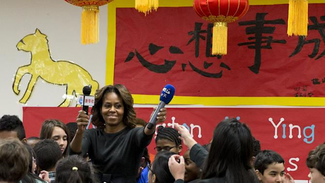 First lady Michelle Obama returns microphones after speaking with a 6th grade class talks about their trip to China, Tuesday, March 4, 2014, at Washington Yu Ying Public Charter School in Washington. In March the first lady is expected to take a trip to China along with her daughters and mother. (AP Photo/Jacquelyn Martin)