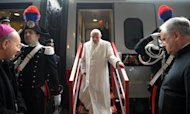 In this photo provided by the Vatican newspaper Osservatore Romano, Pope Benedict XVI, center, leaves a train as he arrives for a peace meeting in Assisi, central Italy, Thursday, Oct. 27, 2011. Buddhist monks, Muslim imams, Orthodox patriarchs and Yoruba leaders have flocked with Pope Benedict XVI to the Umbrian hilltown of Assisi to make an interfaith call for peace and insist that religion must never be used as a pretext for war. (AP Photo/Osservatore Romano) EDITORIAL USE ONLY