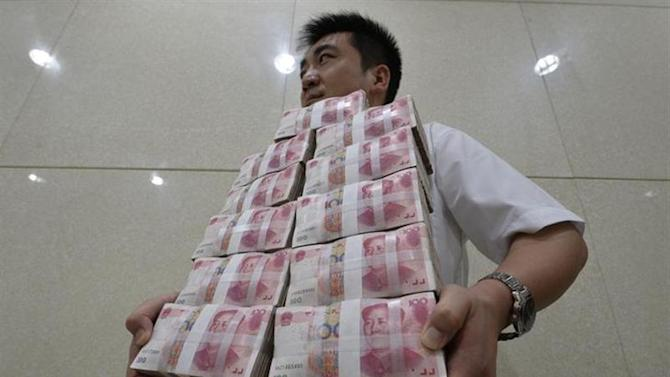 An employee carries bundles of 100 yuan Chinese bank notes to store after counting at a bank in Taiyuan, Shanxi province July 4, 2013.