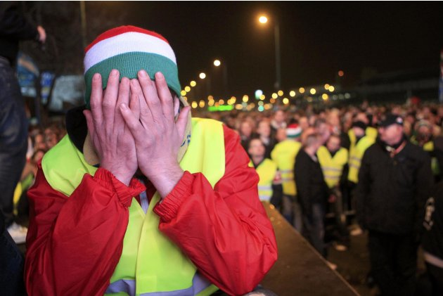 A security guard reacts as far right soccer supporters watch the 2014 World Cup qualifying Group D soccer match between Hungary and Romania on a giant screen outside the stadium in Budapest