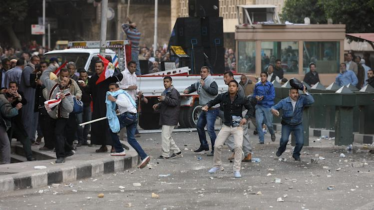 Egyptian protesters throw stones during a clash outside the US embassy in Cairo, Egypt, Friday, March 9, 2012. Several hundred protesters gathered Friday outside the U.S. Embassy in Cairo, raising their shoes at a picture of President Barack Obama and calling on Egypt to expel Washington's ambassador amid a heated national debate about the trial of Americans working with pro-democracy groups who have been charged with using foreign funding to foment unrest. (AP Photo)