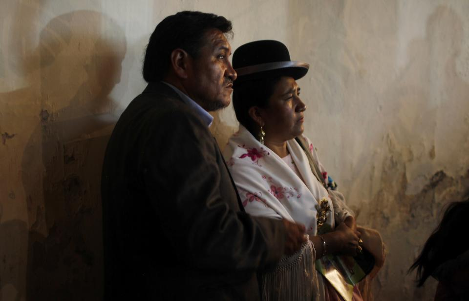 In this Oct. 18, 2013 photo, a couple watches a Chola fashion show by local designers in La Paz, Bolivia. The event, called the Chola Paceña Our Tradition in the 21st Century Fashion Show, is part of an effort to start an Andean modeling school. (AP Photo/Juan Karita)