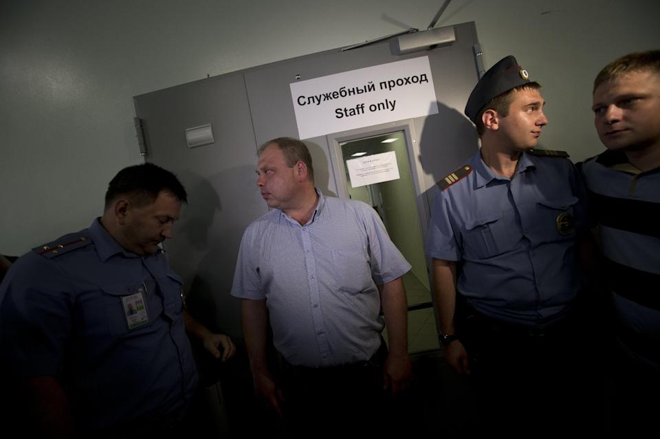 Police block the entrance to a transit zone at Sheremetyevo airport outside Moscow, Russia, Friday, July 12, 2013. Edward Snowden plans to seek asylum in Russia, a Parliament member who was among those meeting with the NSA leaker said Friday. (AP Photo/Alexander Zemlianichenko)
