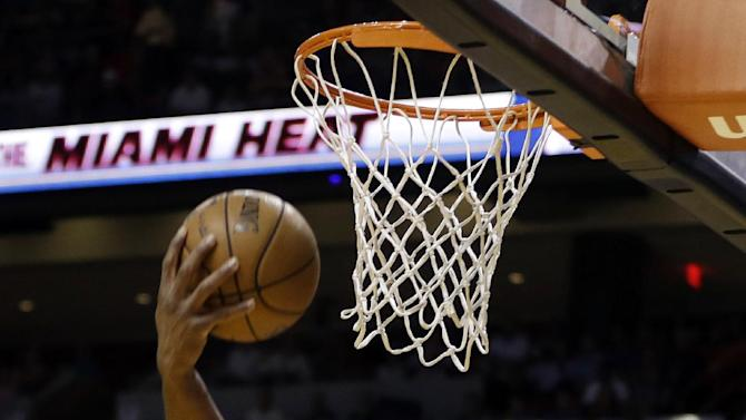 Miami Heat's Dwyane Wade (3) shoots past Atlanta Hawks' Anthony Tolliver (4) during the first half of an NBA basketball game in Miami, Tuesday, March 12, 2013. (AP Photo/J Pat Carter)
