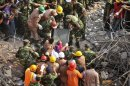 Rescue workers rescue a woman from the rubble of the Rana Plaza building 17 days after the building collapsed in Savar