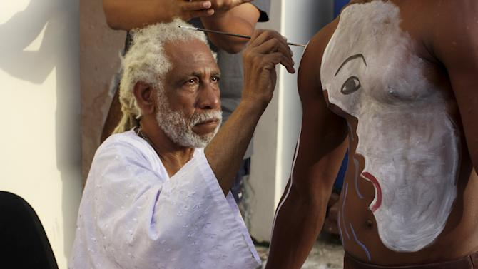 "Cuban artist Manuel Mendive paints a model to perform his creation ""Scape"" during the 12th Havana Biennial, in Havana"