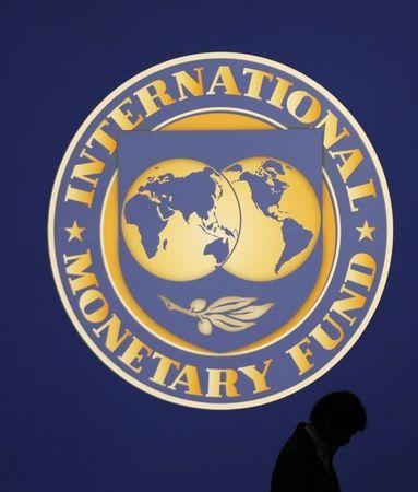 A man walks past the logo of the International Monetary Fund (IMF) in Tokyo