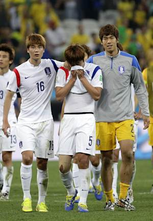 South Korea's Kim Young-gwon, center, is comforted by his teammates Ki Sung-yueng, left, and goalkeeper Lee Bum-young, right, after the group H World Cup soccer match between South Korea and Belgium at the Itaquerao Stadium in Sao Paulo, Brazil, Thursday, June 26, 2014. Belgium beat South Korea 1-0 to top Group H of the World Cup. South Korea was eliminated. (AP Photo/Felipe Dana)