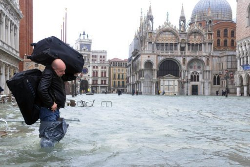 A man carries luggages on a flooded St Mark's Square as floodwaters drenched most of the tourist destination of Venice and led to the evacuation of 200 people in Tuscany.