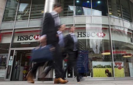 Workers walk past a branch of HSBC bank in central London